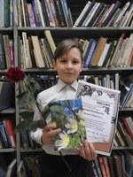 Даниил Франчук на юбилее литературного объединения Россыпи со сборником, в который вошло его стихотворение.jpg